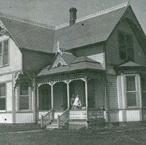 """Image of Elgin Home, Dishman - """"W. I. Dishman house in Elgin, Oregon - Mar. 31, 1900.  Mrs. Dishman and Dan Ruth (Rutch?) [Dan Ruth Dishman, a girl? Dan Ruth or Dan Rutch, a boy?] on porch.  Owned from fall of 1905 to fall of 1909 by J.T. Galloway."""""""