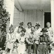 """Image of Union Group, Porch - Margaret """"Aunt Maggie"""" Bell (wearing the dark colored dress and hat) sits on the steps of a porch next to her minister who is holding a dog on his lap.  There are six other women in the picture who are unidentified."""