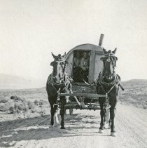 """Image of Union Home, Wagon - """"These men came from Idaho - 1922.""""  The wagon they are riding in appears to have been built with a hard cover, and even has a smokestack."""