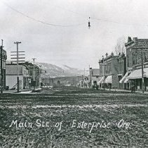 """Image of Enterprise, Business Block - """"931. Main Street of Enterprise, Ore.""""  The W.J. Funk & Co. store is on the corner of the street in the left side of the image, and the Enterprise Mercantile & Milling Co. is on the opposite corner of the street in the right side of the image."""