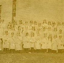 "Image of Flora School, Patriotic Girls - ""Flora School - Photo of all girls wearing white dresses with sashes, hats with a large star on them, and holding small American flags."""