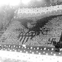"""Image of Cove, Cherry Fair Display 5 - """"Fifth Annual Cherry Fair - 1915 - Cove, Oregon.  Cherry display with a bald eagle and federal shield design in the middle and swastikas in the bottom corners.  [Note added:  The swastika at the time was a form of the Greek cross with the arms bent at right angles, before it was ever associated with the Nazi's.]""""  [Very similar to the photographic print image:  2010.15.00748]"""