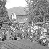 "Image of Cove, Cherry Fair Crowd 1 - ""Fifth Annual Cherry Fair - 1915 - Cove, Oregon.  A large crowd is gathered in front of a wooden platform.  Automobiles and a building are visible in the background."""