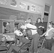"""Image of 1958 Theater Makeup Room - """"1958 Dramatics""""  Cast members sit in front of mirrors while other theater students apply their makeup."""