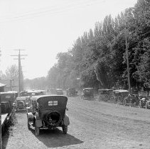 Image of Cove, Street Scene 6 - Cove, Oregon street scene.  Automobiles are parked on both sides of a dirt road.  [Image most likely taken by photographer, Mae Stearns.]