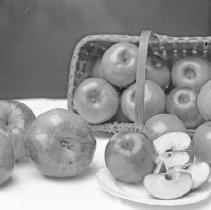Image of Cove, Apples - Apple slices and whole apples arranged with a basket that is laying on it's side - circa 1914.  Probably grown in the area of Cove, Oregon.