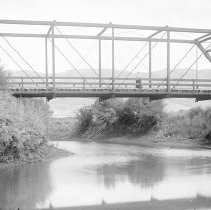 Image of GRV, Bridge - An unidentified woman is standing near the middle of a bridge that spans a small river.