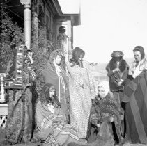 Image of GRV, Lawn Group 1 - A group of women are gathered on the lawn outside the home of Mrs. Rice - circa 1910.  They are all wrapped in various blankets.  [The same house is pictured in 2010.15.02150]
