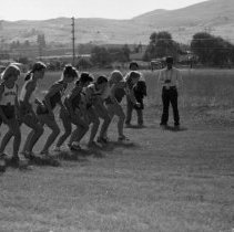 """Image of 1980 Cross Country Start Line 1-1 - """"October 1980""""  Coach Gary Feasel fires off a starter's pistol as young women stand poised along the starting line to take off.  The competition pits cross country team members from EOSC against their counterparts at North Powder and Whitman."""