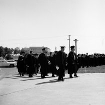"Image of 1970 Graduation, Faculty Walk - ""1970 Graduation""  Three images of the faculty walking in a procession towards Quinn Coliseum where the graduation ceremonies will be held.