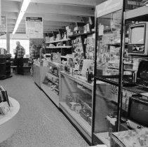 Image of 1974 Students, Shopping 10 - Three images of a young man and woman shopping in a music store where a store salesman shows them the available stereo equipment and sound systems.