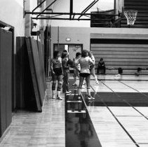 """Image of 1981 Women's Basketball Practice - """"12/2/1981""""  An image of the women's basketball team practicing casually in the main Quinn gymnasium."""