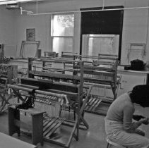 """Image of 1985 Classroom, Textiles - """"1/1985 - Campus candids""""  Five images of a student using a spinning wheel in a textiles classroom.  Large looms fill the classroom behind her."""