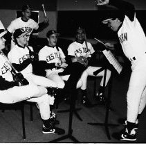 "Image of 1991 Baseball, Cover Photo 1-2 - ""2/11/1991 - Baseball cover photo""  Standing: Scholzen (left), Craig Chastain (middle), Rob Cushman (right, conducting). Seated from left to right: Michael Spencer, J.R. Sisk, Bob Seminoff, Kris Kaelin [or Kaehlin]."