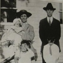Image of 3050 - Unknown Churchville Family, Man, woman holding a baby and two young boys dressed up.