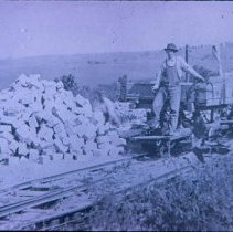 Image of Rail rock car and cut stone pile at East Sioux Falls Quarry, n.d.