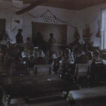 Image of Teacher and students inside school building in Nemo, SD, 1903