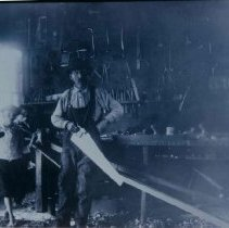 Image of Julius Heberlein (with saw) in his Wagon Shop in Hartford, SD, ca. 1900
