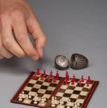 Image of Miniature Chess Set, with hand
