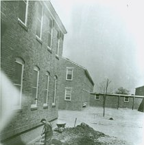 Image of A worker spreads soil along the Administration Building, May 29, 1944 - 2012.23.44