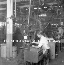 Image of NCR.1998.0595.011 - Com. & Misc. Around The Factory - Factory Interiors - Punch Press #2 - Man Operating A Small Punch Press, Dayton, OH October 13, 1923