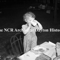 Image of NCR.1998.0604.926 - Old River - Assembly K Picnic - Gail Butts, Daughter Of Mark Butts, Quenches Her Thirst, June 18, 1946