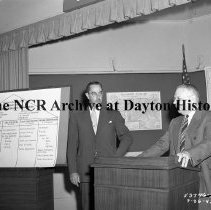 Image of NCR.1998.0912.763 - War Production - Labor-Mangement Committee Meeting - OPA Transportation Award - Two Men At The Podium With A Flip Chart Showing NCR's Transportation Plan, Dayton, OH July 26, 1945