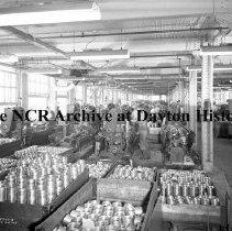 Image of NCR.1998.0913.708 - War File, Rocket Department - Men Working At Machines - View Of The Factory Floor - Rocket Parts In The Foreground, Dayton, OH July 26, 1945
