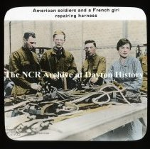 Image of NCR.1998.L0348.094 - Lantern Slides - WWI -  American Committee for Devastated France -  American soldiers and a French girl repairing harness