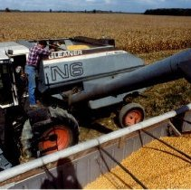 Image of A C Gleaner combine side view unloading corn                                                                                                                                                                                                               -