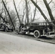 Image of 1925 two new fire trucks parked just off of the road                                                                                                                                                                                                       - 1925