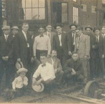 Image of 16 unknown men and an unknown boy in front of a brick building posed by a railroad track and train axle. -