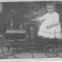 Image of Small Child in Dress Stands in Large Locomotive Toy - Small photograph depicting a child in a dress standing in a large toy ride on pedal locomotive.