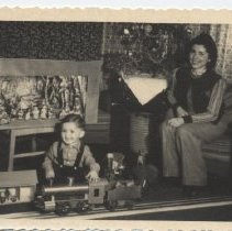 Image of German Christmas Photo of Mother and Baby with Large Toy Train - Small photograph of mother and baby at Christmas.  Mother sits beside Christmas tree on couch and baby plays on floor with large toy train on wooden track.