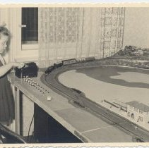 Image of Young German Girl Plays with Toy Trains on Layout - Young German Girl operates transformer on HO gauge layout.