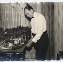 Image of German Man Plays with HO Gauge Layout - German Man Playing with HO gauge layout.  Trains and Crane are Marklin .