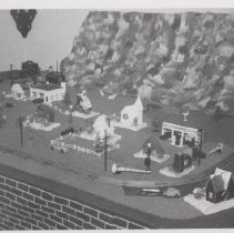 Image of Toy Train Layout with Farm and Mountain Scenery - Basement toy train layout with farm and mountain scenery.  Lionel train with a 1033 transformer & Lionel bridge.  Both Plasticville and cardboard Christmas village buildings with Plasticville accessories.