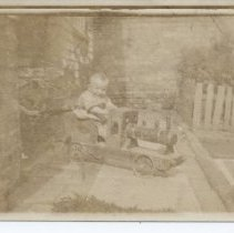 Image of Toddler on Ride-On Steam Locomotive Toy - Early photograph of toddler on handmade wooden ride-on steam locomotive.