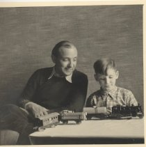 Image of Berlin Photo of Father and Son with Toy Train Set - Father and son sit at table with toy train set.