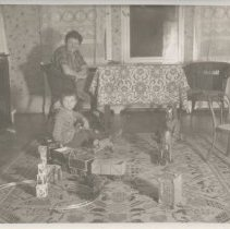 Image of Mother and Son with Toy Trains - Photo of mother and son. Mother sits at table watching son who plays with clockwork toy train on floor.  German photo.   Also shown is a floor or riding train and a riding horse.