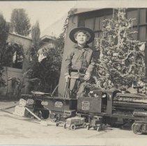 Image of Billy Nevitt with Keystone Ride-On Train Set - Photo of young boy, Billy Nevitt, age 2 years 10 months standing with Keystone 6400 or 6500 ride-on train set.  1933 Christmas photo.
