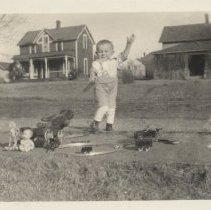Image of Small Boy Outdoors with Toy Train, Doll and Toy Car - Photograph of  small boy outdoors.  His arm is raised and at his feet is a clockwork train set on a circle of track, a toy car and doll.  Photo P2007.176.002 is of the same subject.