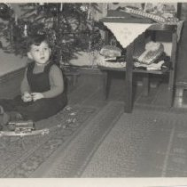 Image of German Toddler under Christmas Tree with Toy Train Set - German photograph of small boy, Rudolf,  in jumper under Christmas tree with clockwork toy train.