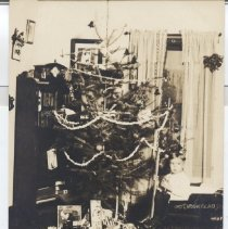Image of Byron and First Christmas Tree - Photo postcard of young boy, Byron, sitting on wagon beside Christmas tree with toy train set on floor.  Ives #1 locomotive, FE #1 tender, 2- #54 gravel cars & # 56 (white) caboose.  Source Greenberg, IVES, Voll II, Reienbauch.