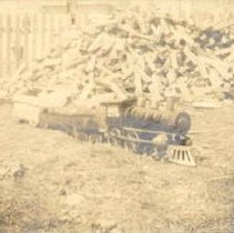 Image of Howard's Toy Train in front of Woodpile - Hillclimber locomotive in front of woodpile.  Schiebleor or Dayton 4-4-0 around 1910-1912.  Dayton Ohio.