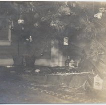 Image of Very Early Photograph of Toy Train under Christmas Tree - Very early photo of toy train under Christmas tree.  Train is a mine locomotive with tram car