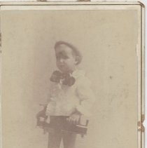 Image of Boy in Bow and Ruffled Shirt with Tin Floor Train - Very early photo of young boy in ruffled shirt and bow tie with tin floor train.