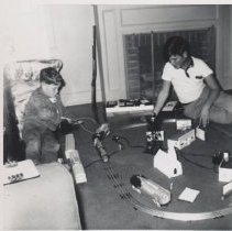 Image of Two Boys Play with Toy Trains on Floor in Front of Fireplace - Photograph of two boys playing with toy trains on floor. Plasticville buildings and Lionel O guage trains.
