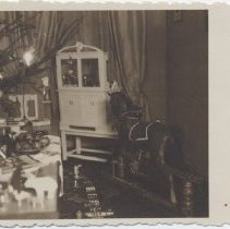 Image of Photo of Christmas Putz under Tree with Toy Trains - Photo of Christmas tree surrounded by Putz and standard gauge toy train on floor.  Rocking horse and cupboard in background.   German.