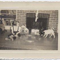 Image of Small Girl with Jack Russell Terrier and Toy Trains - 1950s era photo of  small girl sitting in front of fireplace with Hafner clockwork toy train as Jack Russell terrier investigates her toys.